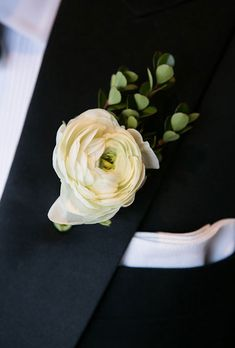 Brides.com: . A boutonniere made of white ranunculus and greenery accents, created by Anna Held Floral Design Studio.