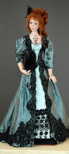 Vivianne 3/5 Description: Silk evening gown circa l896. Gown features three types of lace and bead embroidery. She holds a feather fan and wears an aigrette in her hair. She is 24 inches tall. Painted eyes.