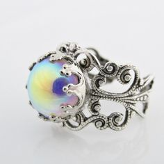 Silver Rainbow Ring, Iridescent Colors, Glass Iridescent Cabochon Ring, Adjustable, Colorful, Iridescent Jewelry by pinkingedgedesigns on Etsy https://www.etsy.com/listing/209456116/silver-rainbow-ring-iridescent-colors