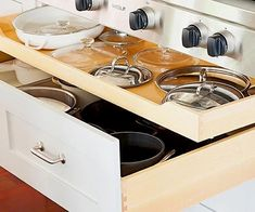 Keep pots and pans in order in a deep drawer under a cooktop. A sliding shelf keeps the drawer organized. Store pots on the lower level and lids above. #drawers #diykitchen