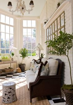 Sunroom. Dark daybed, plenty of plants, natural fiber rug, white brick, window between dining
