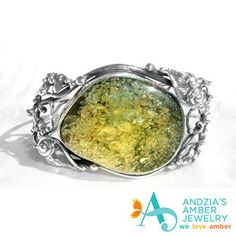 Wondrous green amber cabochon set in fashioned floral motif- curling sterling silver vines create this one of a kind beauty from our Gallery of Sold- Gone, but not forgotten! :D