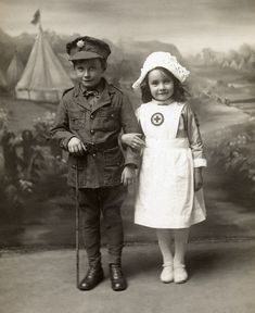 Photo of a small boy & girl in WWI uniforms, 1914.