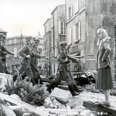 A beautiful French woman watches as German Wehrmacht march on by just shortly after France's capitulation to the German Reich. Summer, 1940.