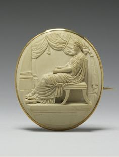 """A Venetian Neoclassical lava cameo brooch, mounted in gold, 1840-1849. The cameo depicting a woman resembling the 1st century BC Roman Empress Antonia Minor, seated on a """"klismos,"""" (a chair with splayed legs)."""