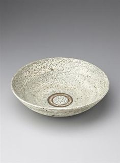 Lucie Rie: Large bowl, Stoneware, blue-green pitted glaze, mineral elements in the body material producing a brown speckle. An unglazed ring in the well. 34.3 cm. (13 1/2 in.) diameter, c.1965