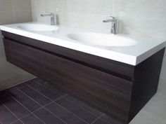 Furniture. Corian Bathroom Vanity Tops Design. Corian Bathroom Vanity Tops With Dark Brown Laminated Wooden Wall Mounted Bathroom Vanity And White Ceramic Double Sink Top And Two Stainless Faucet Together With White Stained Wall Also Black Ceramic Floor.