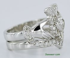 A stunning Claddagh ring in yellow gold with a heart shaped emerald surrounded by diamonds set in white gold. Diamond Claddagh Ring, Claddagh Rings, Wedding Sets, Wedding Rings, Irish Jewelry, Heart Shaped Diamond, Diamond Engagement Rings, Heart Shapes, Celtic