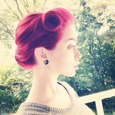 Pin up retro hairdo. Updo with vicotry rolls. Red hair.