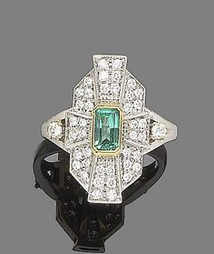 An emerald and diamond plaque ring.  The octagonal plaque, centrally-set with a step-cut emerald, within a brilliant-cut diamond surround, to bifurcated shoulders set with a similarly-cut diamond, diamonds approx. 0.75ct total. Art Deco style.