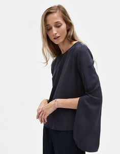 Modern top from Farrow in Slate. Round neckline. Concealed back zip closure. Long bell sleeves with deep slit. Darts at waist. Side slits. Straight hem.  • Lawn • 100% tencel • Hand wash cold