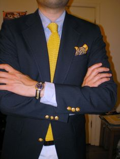 A great combination of navy blazer, bright yellow knit tie, and paisley pattern pocket square.