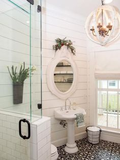 The renovated bathroom, done in uniform white, features a glass enclosed shower and antique style pedestal sink.