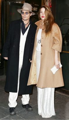 Johnny Depp and Amber Heard. On Amber: wide-legged white pants with a long camel coat and a statement necklace. On Johnny: white pants and a heavy black peacoat with a brown wide-brimmed hat
