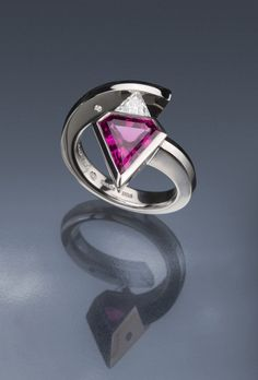 Steven Kretchmer's 2(Stone) Gothic Superman ring in Platinum, with a half-matte finish for the left hand. Featuring a 3.05ct shield-cut Rubellite Tourmaline, a 0.39ct F/SI1 6.0mm point-to-point trillion-cut Diamond, and 0.04ctw Diamond melee stones.