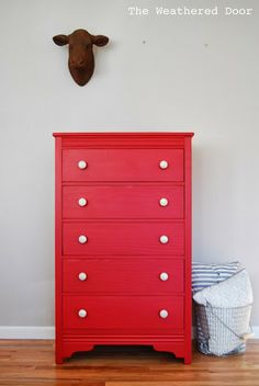 The Weathered Door: A tall red dresser with silver and white knobs
