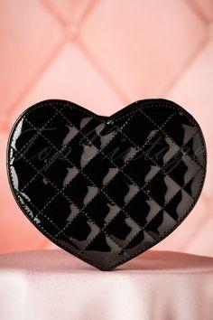 """Deze 60s Eliza Laqcuer Heart Handbagzal jouw hartje veroveren!""""You'll need this bag like a heartbeat!"""" Deze kleine handtas is een echte must-have door de speelse hartvorm en de geruite stiksels. Uitgevoerd in topkwaliteit zwart 'faux' lakleder met verstelbaar en afneembaar hengsel waardoor je haar op veel manieren kunt dragen. Follow your heart... bag! ;-)   Sluit d.m.v. een ritssluiting Zilverkleurige details 2 extra vakjes waarvan é&e..."""
