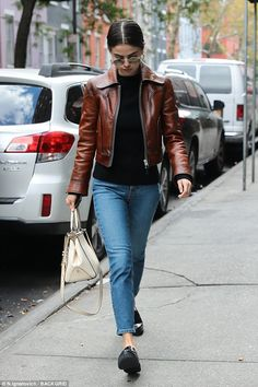 She's got that charisma:The 25-year-old stayed warm in a brown leather jacket with a blac...