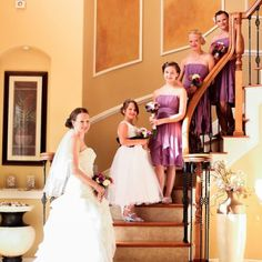 The bride poses with her flower girl and bridesmaids on the steps of the hotel. The purple theme is brought out in the chiffon dresses exuding classic wedding chic! -  Image Credit: Ailyn La Torre Photography