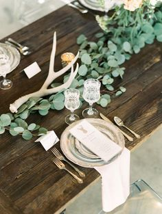 Infuse your tablescape with a country-chic vibe using antlers and lots of lush greenery.