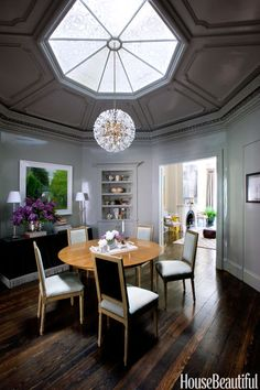 In the octagonal entry/dining room of Nina Farmer's Boston brownstone, Farrow & Ball's Lamp Room Gray in Full Gloss shimmers below the etched skylight and a vintage Sputnik pendant. The Baker Shansi table is ringed by Zentique Louis side chairs. Bright seats and fronts (in Holly Hunt Made in the Suede) contrast with dark backs (Rogers & Goffigon's Biarritz) against the 19th-century pumpkin pine floor. Photograph, Lynn Geesaman.
