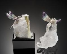 By Peter Mueller Brazil Each dragonfly possessing four carved wings made from Chinese banded fluorite with silver bodies; the first, perched atop a green tourmaline in quartz matrix specimen, set in a black acrylic base, height 4 1/2 in ; the second, set atop a quartz crystal cluster, height 4in (2)