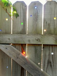Drill holes ever so slightly smaller than your marbles, so they will fit snugly and no adhesive needed.  Sunlit, its sparkles! ... so be sure to pick your area on the fence where the sun goes behind it for the most sparkle...i.e., on the west side if possible, where the afternoon sun will shine on the backside.