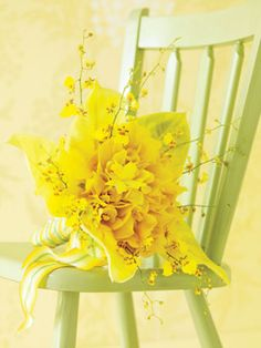 Like a halo of butterflies, oncidium orchids hover around this tropics-inspired bouquet, created by hand-wiring Nevada cymbidium and mini cymbidium orchids, then framing with yellow spathaphylum leaves. Ribbon, May Arts, mayarts.com. Chair, Maine Cottage, mainecottage.com. Floral design by Claire Bean Floral and Event Design, clairebean.com.