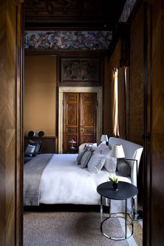 Exterior, Attractive Hotel Interior Design In Bedroom Featuring Cool White Bed Pillow Black Bedside Table Flower Pot With Brown Carved Door Wall Decor Grey Carpet: Aman Canale Grande Hotel with Exclusive Interior Completing Your Vacation in Floating City in Venice
