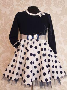 Niesamowita sukienka wykonana z dzianiny oraz tiulu. Dół kreacji odszyty podszewką, a góra sukienki udekorowana elegancką kokardką oraz perełkami. Sukienka posiada długi rękaw oraz kryty zamek. Atłasowa tasiemka w pasie wiązana z tyłu pozwala na dopasowanie sukienki.