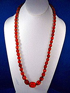 Golden Amber Faceted 27 Inches long Graduated Necklace with a twist Clasp from the 40s and 40 Grams. The Large center bead is 7/8 of an inch. The picture shows Red but it is actually Honey Golden.