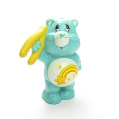 "This vintage Care Bears miniature figurine is ""Wish Bear Holding a Wishbone."" Wish Bear is teal blue with a yellow shooting star on her tummy and is holding up a yellow wishbone. Wish Bear has a few m"