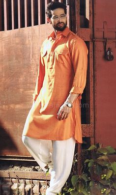 Get the raw and rugged look of Shah Rukh Khan from Raees with this classy Pathani Suit having Orange kameez made from Dobby fabric. Comes with contrast Modal fabric White bottom. Punjabi Kurta Pajama Men, Kurta Men, Boys Kurta, Pathani Suit Men, Pathani Kurta, Indian Groom Wear, Indian Wear, Indian Male, Indian Men Fashion