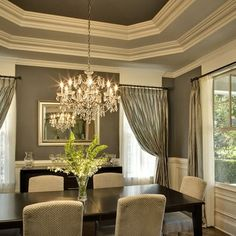 Gorgeous dining room with tray ceiling painted medium gray on steps and darker gray on the flat upper ceiling.