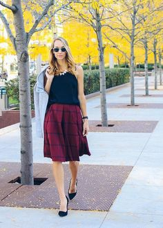 This burgundy check pleated midi skirt is perfect for a fall stroll. The Fox and She pairs it with a black blouse, gray coat, and chic black heels   Banana Republic