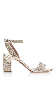 This sandal by Tabitha Simmons is a new take on classic style by the designer, rendered in gold glitter fabric and features a block heel and ankle strap. Preorder now on Moda Operandi