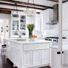 Reclaimed-oak beams shelter the kitchen, which is equipped with a Viking hood and cooktop and Calacatta gold marble counters | archdigest.com