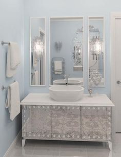 this shade of blue usually unnerves me, but this one is well accessorized. chandeliers, large mirrors, metallic vanity...so pretty.