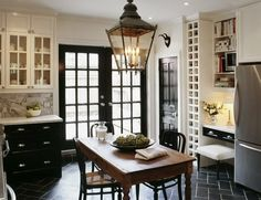 Black Herringbone Tile with White Grout, Carrara Marble Counters, White Cabinets with Glass Fronts and Black Cabinets, Lantern Light and an Antique Wood Table...What's Not To Love?!