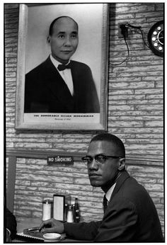 Malcolm X beneath a picture of the Most Hon. Elijah Muhammad,1961.