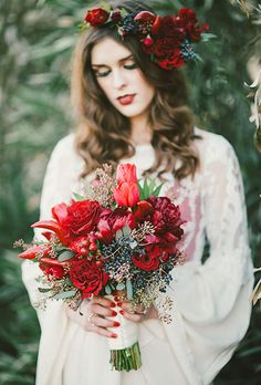 Brides.com: . A winter wedding bouquet with red peonies and roses, chili peppers, and berries, created by RLove Floral Designs.