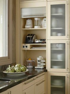 Vertically shelved appliance garages take visual weight off the counter and save space. This design utilizes corners to preserve maximum storage area.