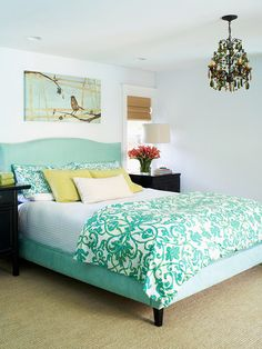 Coloring Inside the Lines: With an upholstered headboard and side rails, there's no need to fuss with a bed skirt. The streamlined look provides the perfect foundation for a mix of textured linens in this bedroom. A long and lean piece of neat art echoes the straight lines of the bed. chandelier