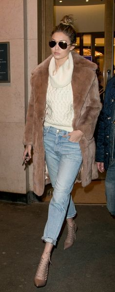 Gigi Hadid in an oversized turtleneck sweater, boyfriend jeans, and a faux fur coat.