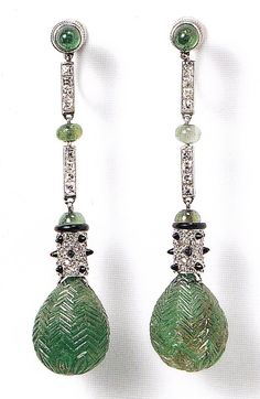 A pair of Art Deco pendant earrings, by Cartier Paris, circa 1922. Emeralds, onyx and diamond set in platinum; chain of square-cut diamonds and emerald beads, with pavé-set diamond cylinders studded with onyx; pear-cut emeralds engraved with a chevron pattern. Image source: Cartier, by Hans Nadelhoffer #Cartier #ArtDeco #earrings