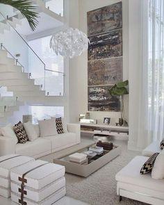 Linda sala de estar clean com pé direito duplo. A obra de arte na parede tem destaque e dita a paleta de cores que complementam a sala. Muito refinada!