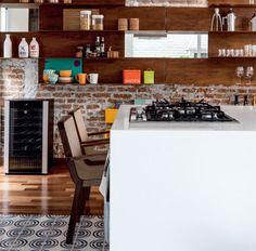 Com 90 cm de altura, a ilha de Corian abriga o fogão e a mesa de jantar 2.88, da Ovo, que fica encostada à peça. As cadeiras Terceira são da mesma loja. Potes da Doural, leiteiras da Fulana Guaçú e bules e espremedor da Benedixt.