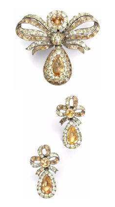 An 18th century topaz and chrysoberyl pendeloque pendant and pair of earrings, Portuguese. Each bow surmount suspending a pear-shaped drop, set throughout with vari-cut topaz and chrysoberyls in foiled, closed-back silver settings, pendant length 6.2cm, earring length 4.4cm, fitted case