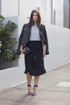 The Midi Skirt and Leather Jacket Combo Is One Youll Want to Try ASAP - over-the-shoulder leather jacket + black midi skirt with flirty ruffled seam and barely-there sandals