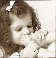 sibling kissing newborn feet - think this one is a little ambitious but a gentle kiss would be a great photo
